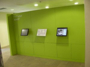 green wall divider with two screens fitted in the middle