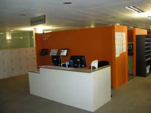 reception are in front of an orange cubicle behind with desktops and office chairs