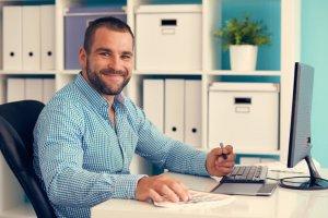 smiling graphic designer working on a digital tablet in front a desktop