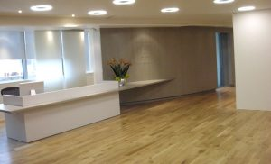 reception area with parquet flooring, bronze curved walls and all white reception desk