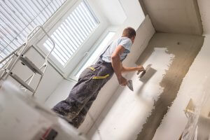man plastering office walls with float and plaster